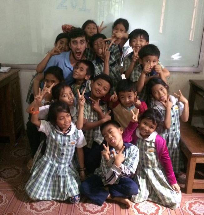 Anthony Nelson surronded by a crowd of children in Cambodia