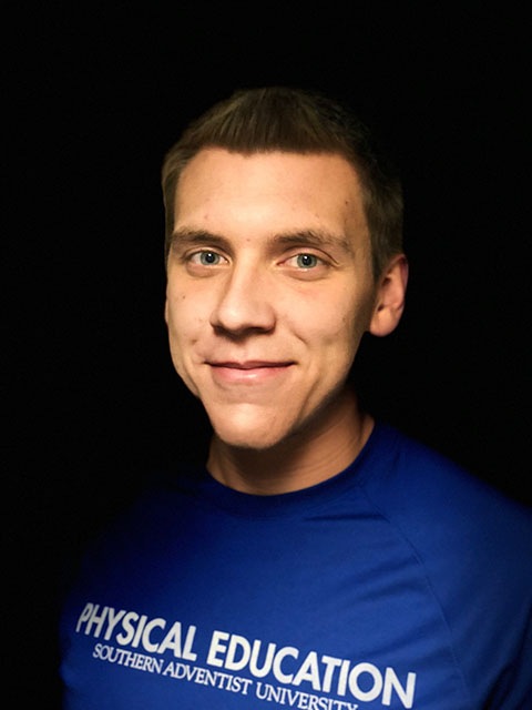 portrait of young man wearing a blue shirt in a black background
