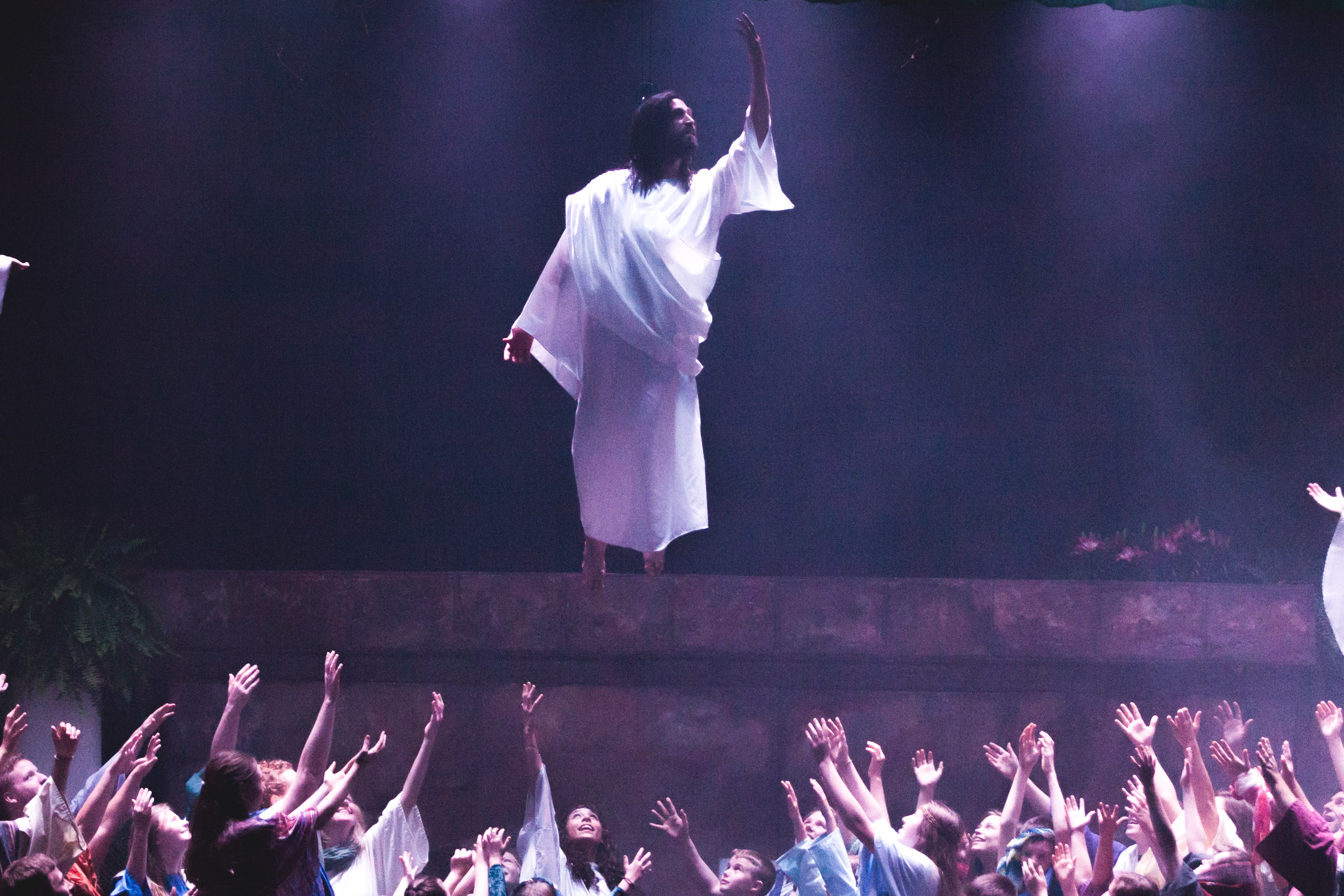 Jesus is lifted off the stage as believers raise their hands